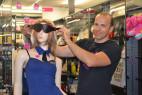 Adam předvádí koženou masku v prodejně na figuríně